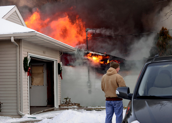 "BEN MIKESELL | THE GOSHEN NEWS<br /> Steven Bigler of Goshen watches the house fire next door Tuesday morning on the 16000 block of C.R. 40 in Goshen. ""My wife was hearing things and I only noticed the fire when I walked out of my garage,"" Bigler said. ""The side of my house is completely melted off."""