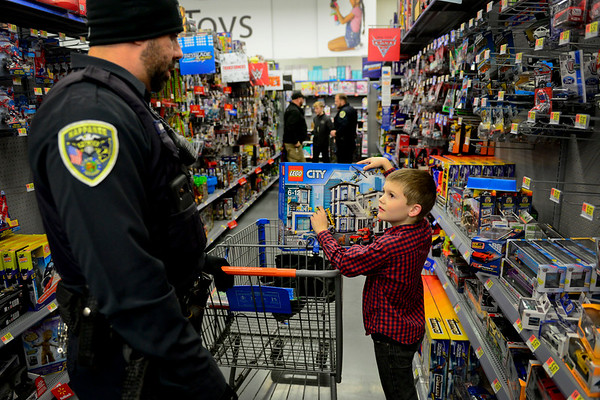 "BEN MIKESELL | THE GOSHEN NEWS<br /> Kalob Carr, 8, of Nappanee, picks out toys with Nappanee police officer Dan Hawkins during Wednesday's Cops and Kids event at Walmart on Elkhart Road. ""I feel like I won the lottery,"" Carr said as he placed toys in the cart."