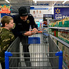 "BEN MIKESELL | THE GOSHEN NEWS<br /> Zethen Henry, 8, of Nappanee goes over his shopping list with Nappanee police officer Nik Havert during Wednesday's Cops and Kids shopping event at Walmart on Elkhart Road. ""He wants to buy stuff for his family and friends,"" Havert said. ""He hardly wants anything for himself."""