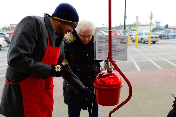 BEN MIKESELL | THE GOSHEN NEWS<br /> Interra Credit Union employee Matt Wells helps Sally Nusbaum of Goshen donate money to the Salvation Army on Wednesday outside Walmart in Goshen.