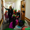 BEN MIKESELL | THE GOSHEN NEWS<br /> West Goshen kindergarten teacher Katrina Godzisz knocks on a resident's door Wednesday at Greencroft Goshen. She lead students through the halls while they sang christmas carols and handed gift bags to residents.