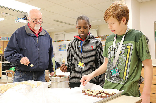 JOHN KLINE | THE GOSHEN NEWS<br /> Bob Duell, a mentor with the Goshen Middle School E3 Survival Skills for Life program, left, works with E3 seventh-graders during a holiday cookie-baking service project at the school Friday afternoon.