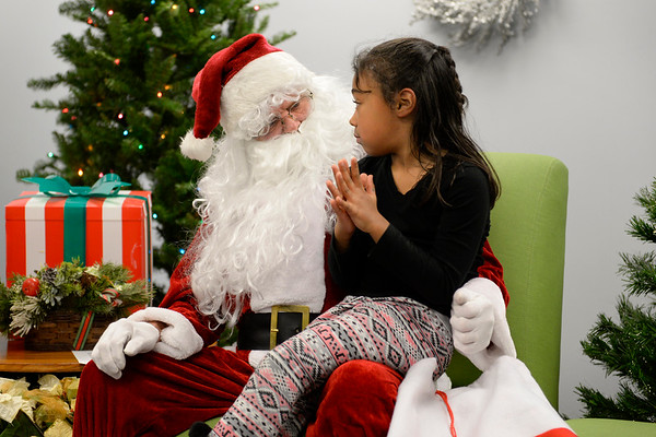 BEN MIKESELL | THE GOSHEN NEWS<br /> Joe Tusing of Elkhart, dressed as Santa, listens to seven-year-old Destinee Hall of Elkhart as she describes what is on her Christmas list Dec. 18 at the Elkhart Public Library.