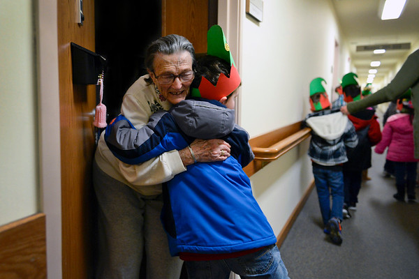 BEN MIKESELL | THE GOSHEN NEWS<br /> Aiden Linn, a kindergartener at West Goshen Elementary, hugs Greencroft Goshen resident Gladys Hodge after his classmates sang a Christmas carol for her Wednesday. Kindergarteners and first-graders from West Goshen spent their money from Mayor Jeremy Stutsman's Year of Goodness initiative on goodie bags which they handed out to residents at Greencroft while caroling through the halls.