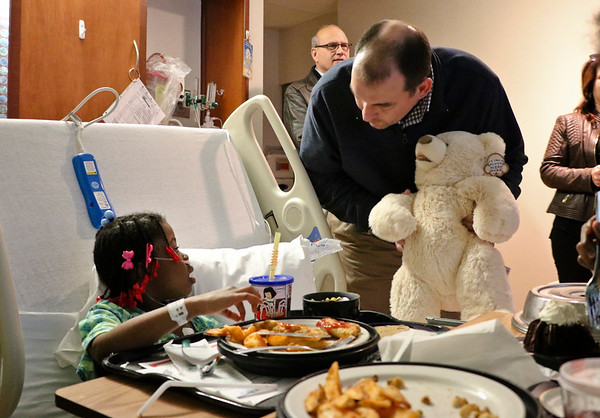 LEANDRA BEABOUT | THE GOSHEN NEWS<br /> Five-year-old Jalaunie Birdsong looked up from her lunch, surprised to see Aaron Kobb, director of admin and finance at South Bend International Airport, giving her a teddy bear for Christmas.