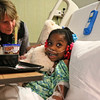 "LEANDRA BEABOUT | THE GOSHEN NEWS<br /> Michaela Nufer, director of women and children's services at Elkhart General Hospital, helps Jalaunie Birdsong, 5, settle in with her new teddy bear while Birdsong, smiling and speechless, looked up at the ""Bears in the Air"" visitors from South Bend International Airport."