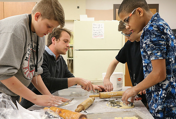 JOHN KLINE | THE GOSHEN NEWS<br /> Martin Hofkamp, a Goshen Middle School teacher and mentor with the school's E3 Survival Skills for Life program, second from left, works with E3 seventh-graders during a holiday cookie-baking service project at the school Friday afternoon.