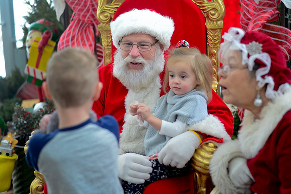 BEN MIKESELL | THE GOSHEN NEWS<br /> Lexi Leininger, 2, of Mishawaka sits on Santa's lap Dec. 9 at Linton's Enchanted Gardens.