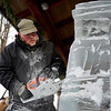 BEN MIKESELL | THE GOSHEN NEWS<br /> Ryan Frauhiger of Bluffton uses a chainsaw to carve his ice sculpture Friday outside of Davis Mercantile in Shipshewana. This is Frauhiger's second year participating in the Shipshewana Ice Festival sculpture contest. Though he usually carves wood sculptures, he said he enjoys the challenges of carving into ice.