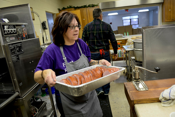 BEN MIKESELL | THE GOSHEN NEWS<br /> Susie Hooley, coordinator for the Christmas dinner at First Presbyterian Church, moves around the kitchen with a tray of ham Saturday. Hooley expected to serve nearly 800 guests Monday.
