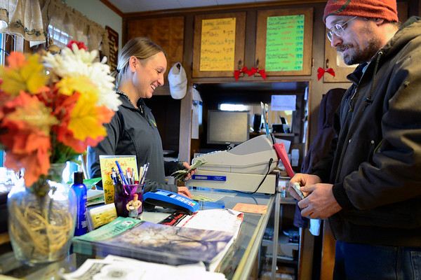 BEN MIKESELL | THE GOSHEN NEWS<br /> Jessica Watson helps Alan Cundiff purchase chicken feed Thursday at Jack's Feed Shack in Bristol. Cundiff drives from Scott to buy his feed.