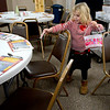 BEN MIKESELL | THE GOSHEN NEWS<br /> Six-year-old Eloise Yacks of Goshen helps set the tables Saturday for the Christmas Dinner at First Presbyterian Church. Placemats for the dinner were decorated by the Boys and Girls Club of Goshen.