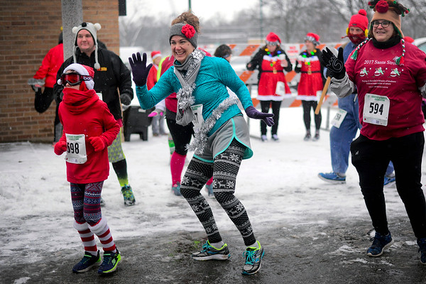 BEN MIKESELL | THE GOSHEN NEWS<br /> Danielle Carrington of Middlebury breaks into dance with her son Drew, 8, while stretching before the Santa 5K run Saturday in Elkhart. This is the Carrington's first time participating in the run.