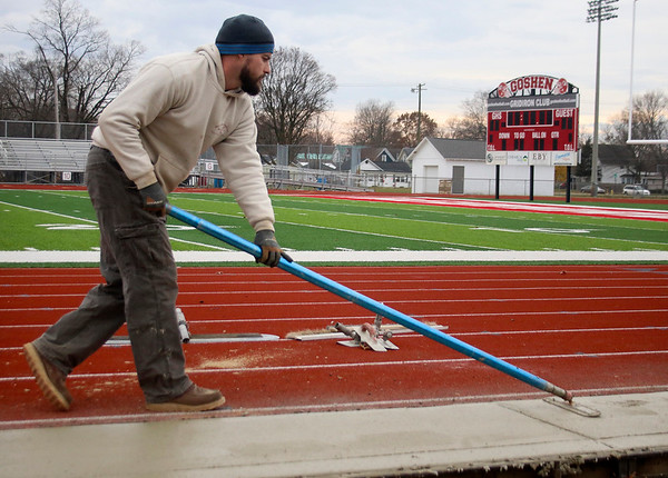 BEN MIKESELL   THE GOSHEN NEWS Tim Denlinger of Goshen smooths out a concrete sidewalk Monday afternoon at Goshen High School's Foreman Field, prior to the installation of the field's new bleachers. His family's business, J.L. Denlinger Concrete, spent the afternoon flattening and grooving lines in the new sidewalk. The $900,000 replacement plan for the bleachers was approved in August, and is slated to be complete in the spring.