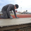 BEN MIKESELL | THE GOSHEN NEWS Tom Denlinger of Elkhart smooths out a concrete sidewalk Monday afternoon at Goshen High School's Foreman Field, prior to the installation of the field's new bleachers. His family's business, J.L. Denlinger Concrete, spent the afternoon flattening and grooving lines in the new sidewalk. The $900,000 replacement plan for the bleachers was approved in August, and is slated to be complete in the spring.