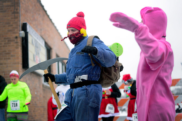 BEN MIKESELL | THE GOSHEN NEWS<br /> Dressed as Yukon Cornelius, Scott Perry of Goshen dances to warm up prior to the Santa Stroll on Saturday in Elkhart. Perry won this year's Best Costume award.