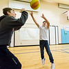 JAY YOUNG | THE GOSHEN NEWS<br /> West Goshen Elementary student Colton Rapp fires a shot over Goshen High basketball player Austin Cain after school on Monday afternoon. Players from the Goshen High boys basketball team visited West Goshen Elementary for an hour Monday after school and spent time reading, playing games and shooting hoops with students at the school.