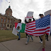 JAY YOUNG | THE GOSHEN NEWS<br /> Protesters carrying both Mexican and United States flags march in front of the Elkhart County Courthouse on Thursday afternoon.