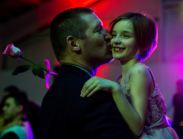 JAY YOUNG | THE GOSHEN NEWS<br /> Holding a rose, seven-year-old Caroline Damer gets a kiss from her dad Brent, both of Goshen, as they slow dance during the Daddy Daughter Valentine's Dance hosted by Goshen Parks and Recreation on Thursday evening at the Elkhart County fairgrounds.