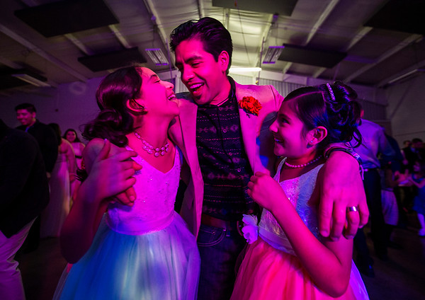 JAY YOUNG | THE GOSHEN NEWS<br /> A pink light shines on Jonathan Baez as he puts his arms around his daughters Maya, 11, left, and Hannia, 9, right, while they dance during the Daddy Daughter Valentine's Dance hosted by Goshen Parks and Recreation on Thursday evening at the Elkhart County fairgrounds.