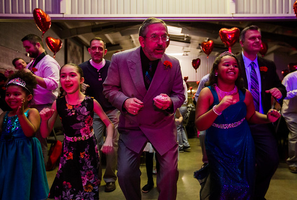 JAY YOUNG | THE GOSHEN NEWS<br /> Gene Thompson, center, does the chicken dance with his granddaughter Abigail, right, and others during the Daddy Daughter Valentine's Dance hosted by Goshen Parks and Recreation on Thursday evening at the Elkhart County fairgrounds.