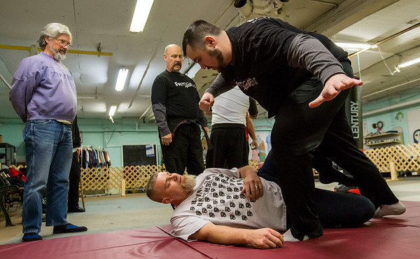 JAY YOUNG | THE GOSHEN NEWS<br /> Army veteran Kenny Holmes hovers over Marine veteran Bill Campbell as Holmes demonstrates the importance of keeping an arm up to defend after a fall during a martial arts training session on Feb. 9, 2017 in Elkhart.