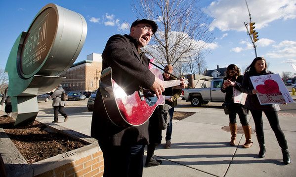 JAY YOUNG | THE GOSHEN NEWS<br /> Jason Springs, of South Bend, leads a small group of protesters in a song in front of the Goshen Chamber of Commerce building Tuesday afternoon. The protesters were there because a representative for U.S. Rep. Jackie Walorski was meeting with the public from 3 to 5 p.m.