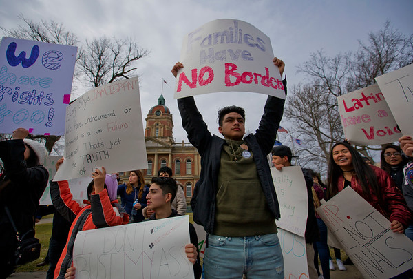 "JAY YOUNG | THE GOSHEN NEWS<br /> Goshen High student Chris Serrano holds up a sign that reads ""Families have no borders"" while protesting for immigration rights Thursday afternoon in front of the courthouse."