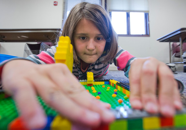 JAY YOUNG | THE GOSHEN NEWS<br /> Nine-year-old Jaquie Burkholder, of Middlebury, concentrates as she carefully places a Lego brick as she builds a border around her yellow heart during a Lego Club meeting Tuesday afternoon at Middlebury Public Library.