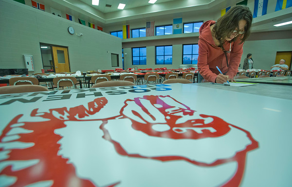 JAY YOUNG | THE GOSHEN NEWS<br /> Norma Jean Lopez, of Osceola, places a bid on an old Goshen Redskins sign during a silent auction in the cafeteria of Goshen High School on Friday evening. The school was auctioning off old Redskins clothing and memorabilia.