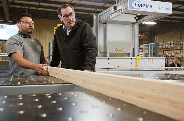 "JAY YOUNG | THE GOSHEN NEWS<br /> Robert Weed Plywood employee Jose Pineda, left, shows U.S. Senator Joe Donnelly how to operate a machine at the factory during a ""Donnelly Days"" event on Monday morning."