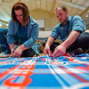 JAY YOUNG | THE GOSHEN NEWS<br /> Interra employees Ashley White and Charlie Miller, both of Goshen, spend Monday afternoon creating a Chicago Cubs fleece blanket for Project Linus during a staff development event at Grace Community Church. The hour long service event, named Power of the Hour, featured about 250 Interra employees working on a variety of projects. Besides the blankets, other projects included appreciation goody bags for local firefighters and EMTs, creating grief masks for Ryan's Place and packing single serving sized food items and laundry detergent for The Window.