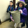 SHERRY VAN ARSDALL | THE GOSHEN NEWS Zarin Jamesen, 6, Goshen, and his sister, Macy Jamesen, 9, hold onto a bucket and cover during a backyard maple syrup workshop at Bonneyville Mill County Park in Bristol Saturday.