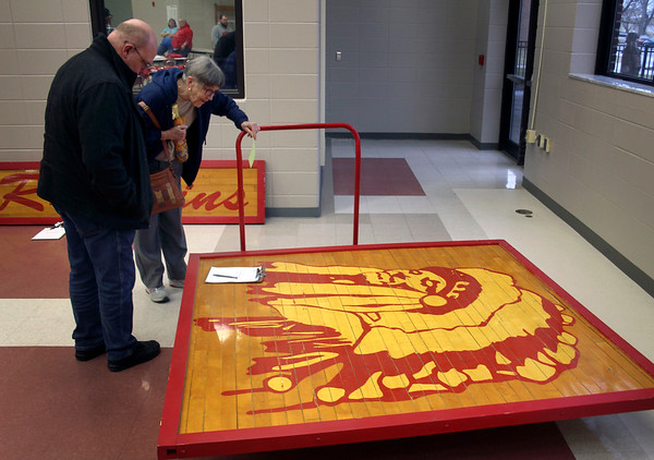 JOHN KLINE | THE GOSHEN NEWS<br /> Goshen residents Jon Millard, left, and Barbara Hay examine a section of old Goshen High School gym floor containing the image of a large Indian Chief's head during a silent auction in the school's cafeteria Friday evening. The school was auctioning off old Redskins clothing and memorabilia.