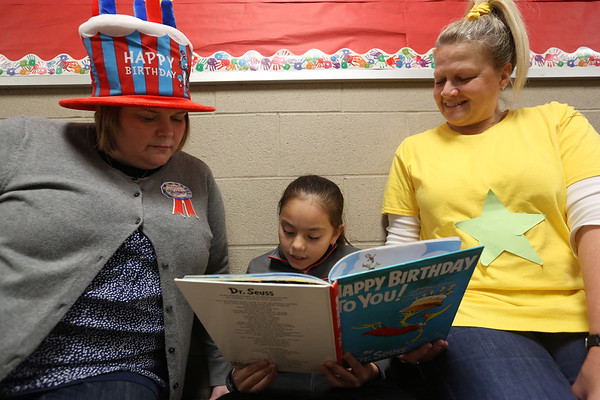 "JAY YOUNG | THE GOSHEN NEWS<br /> Waterford Elementary third grader Yesenia Moreno-Reyes reads ""Happy Birthday To You,"" by Dr. Seuss, to third grade teacher Kristy Moberg, left, and paraprofessional Jenni Bontreager on Thursday morning. Thursday was Dr. Seuss' 113th birthday."