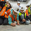 JAY YOUNG | THE GOSHEN NEWS<br /> Syracuse Elementary third-grade student Sophia Smith signs her name on a concrete slab it what will become the principal's office during a tour of the new elementary school that is still under construction on Thursday morning.