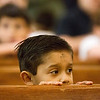 JAY YOUNG | THE GOSHEN NEWS<br /> St. John the Evangelist Catholic School kindergartener Oliver Herrera peers over the top of a pew as he watches other parishioners receive ash crosses on their foreheads during an Ash Wednesday Mass at the church. Ash Wednesday marks the first day of Lent.