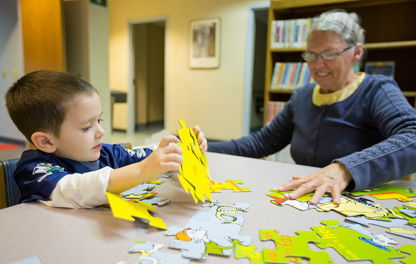 JAY YOUNG| THE GOSHEN NEWS<br /> Three-year-old Brayden Beachy, of Goshen, pulls apart pieces of a Dr. Seuss puzzle at the Goshen Public Library on Wednesday morning. Beachy was putting together the puzzle with his grandmother, Rose Beachy.