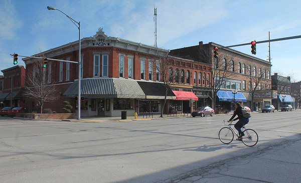 Roger Schneider | The Goshen News<br /> A bicyclists rides across the Main and Washington street intersection in downtown Goshen Monday. The historic buildings in the downtown district have been deemed one of the strengths of the area in a downtown action plan.