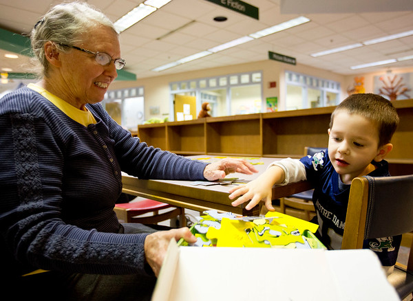JAY YOUNG| THE GOSHEN NEWS<br /> Three-year-old Brayden Beachy and his grandmother Rose Beachy, both of Goshen, put away a Dr. Seuss puzzle after trying to put it together Wednesday morning at the Goshen Public Library.