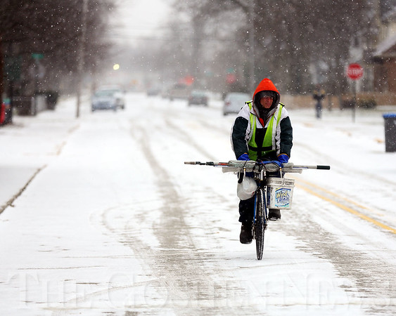 JAY YOUNG | THE GOSHEN NEWS<br /> Wearing a yellow safety vest, a cyclist on his way to work carefully navigates a snow covered Washington Street near Fifth Street on Wednesday morning. Winter came roaring back to Goshen on Wednesday, with an expected high of only 22 degrees and snow showers throughout the day. According to the National Weather Service, area residents should not expect any relief from the cold temperatures in the coming days, as highs in the teens and low 20s are forecasted through the rest of the week.