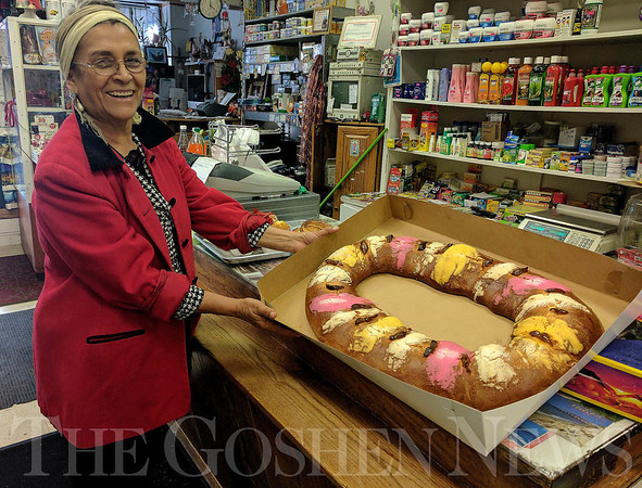 SHEILA SELMAN | THE GOSHEN NEWS<br /> Clara Arevalo displays one of the Rosca de Reyes cakes sold at Gutierrez Mexican Bakery in downtown Goshen Thursday afternoon.