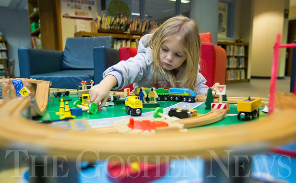 JAY YOUNG | THE GOSHEN NEWS<br /> Three-year-old Bailey Slabach, of Goshen, plays with the train set in the children's area at the Goshen Public Library on Thursday afternoon while waiting for her mother to check out books.