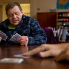 JAY YOUNG | THE GOSHEN NEWS<br /> Joe Lehman checks the cards in his hand while waiting for his turn during a weekly Euchre game Wednesday morning at Gaining Grounds.  Lehman has been playing since 2008, when his family moved away and he needed a new group to play with.