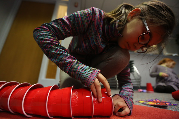 JAY YOUNG | THE GOSHEN NEWS<br /> Ten-year-old Lily Garcia-Bayles, of Goshen, threads together red plastic cups as she creates a dragon Tuesday evening at the Goshen Public Library as part of a book club project.