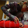 JAY YOUNG   THE GOSHEN NEWS<br /> Ten-year-old Lily Garcia-Bayles, of Goshen, threads together red plastic cups as she creates a dragon Tuesday evening at the Goshen Public Library as part of a book club project.