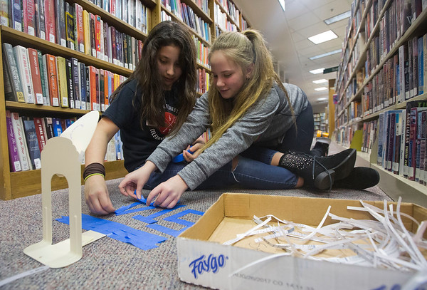 "JAY YOUNG | THE GOSHEN NEWS<br /> Eleven-year-old Saige Hanna reaches over Hannah Alonso, 12, both of Goshen, as they use blue painter's tape to spell out the word ""Start"" at the beginning of hole three of their mini-golf course Friday night at the Goshen Public Library. The teen department hosed Nerd's Night Out at the library. About a dozen teens participated in the event where they used items such as books, book ends, shredded paper, cardboard boxes and even furniture to create a mini-golf course throughout the library."