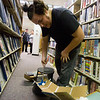 JAY YOUNG | THE GOSHEN NEWS<br /> Between shelves of books, Andrew Garcia uses his putter to try to navigate his golf ball up a cardboard chute and into the hole on Friday night at the Goshen Public Library. The teen department hosed Nerd's Night Out at the library. About a dozen teens participated in the event where they used items such as books, book ends, shredded paper, cardboard boxes and even furniture to create a mini-golf course throughout the library.