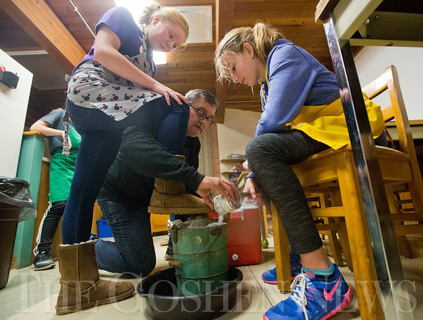JAY YOUNG | THE GOSHEN NEWS<br /> Glenn Stutzman reaches around the leg of Bethany Christian seventh grade student Norah Schloneger to add more salt to the ice cream churner while sixth grade student Mara Schrock turns the crank on Tuesday afternoon at Bethany Christian.