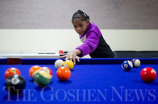 JAY YOUNG | THE GOSHEN NEWS<br /> Fourth grade student Jalisa Turpin lines up a shot while playing pool Monday afternoon at the Tolson Youth Center in Elkhart.